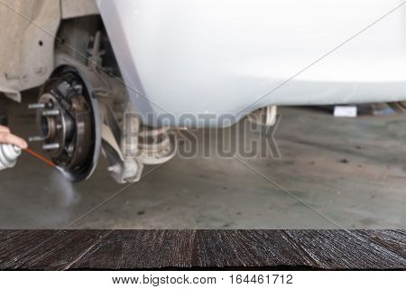 Mechanic Spray Chemical To Clean Brake (blur Image) With Selected Focus Empty Wood Table For Display
