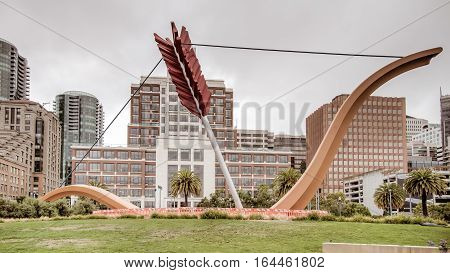 San Francisco, CA, USA - August 3, 2014: A sculpture resembling Cupid's bow and arrow is wedged in the ground alongside the Bay Bridge of San Francisco's Embarcadero