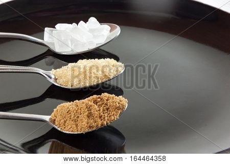 Brown cane sugar and granulated sugar and rock sugar in a metal spoon on the black background. Pure cane sugar for natural.