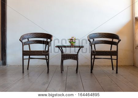Wicker chairs and roses on the wicker middle table.