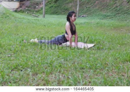 Young Woman Practicing Yoga Exercises Outdoor In Park,  Relax In Nature (blur Image)