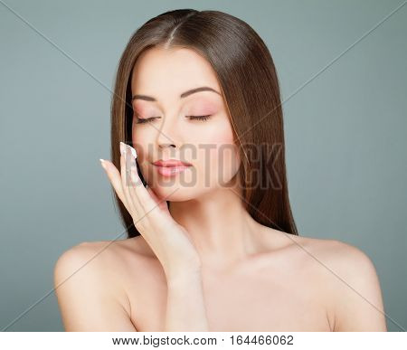 Young Woman Spa Model Applies a Moisturizer to her Face. Skincare Concept