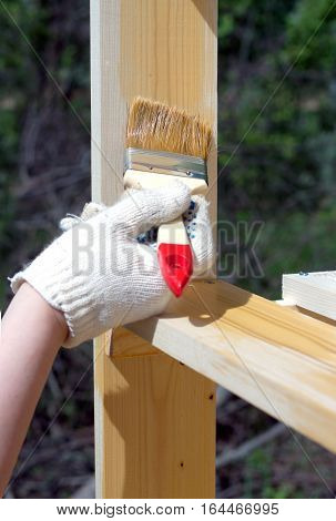 Female hand in textile glove paints wooden shelving outdoors vertical view closeup