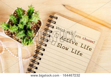 Whick will you Choose? Active life or Slow life in notebook with cactus on wooden background. Conceptual between active life and slow life