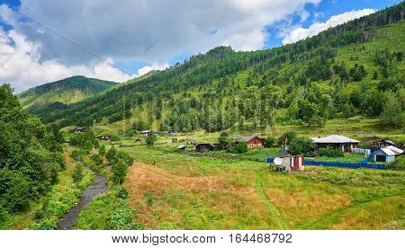 Old wooden houses with gardens in valley of a small stream. Village Maritui. Pribaikalsky National Park. Irkutsk region. Russia
