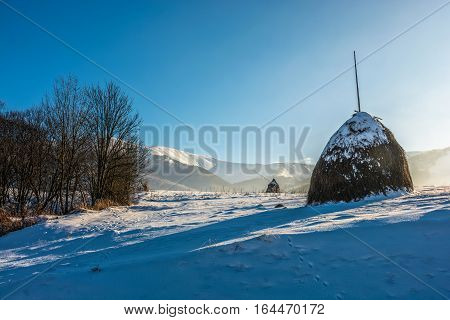 Agricultural Field With Haystack On Hillside In Winter