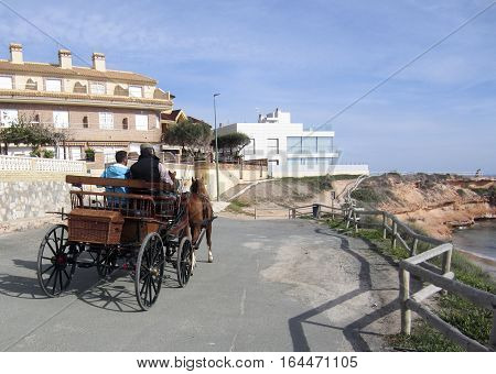 Torrevieja, Spain - November 13, 2016 : Horse drawn carriage runs along coast road at Pilar del Horadada, Costa Blanca. Locals show off the rigs by running around the town, along with others.