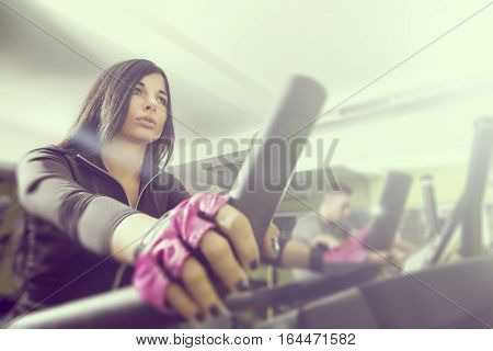 Two young people working out in a gym riding a bike and working out on a ski simulator. Focus on the girl lens flare effect