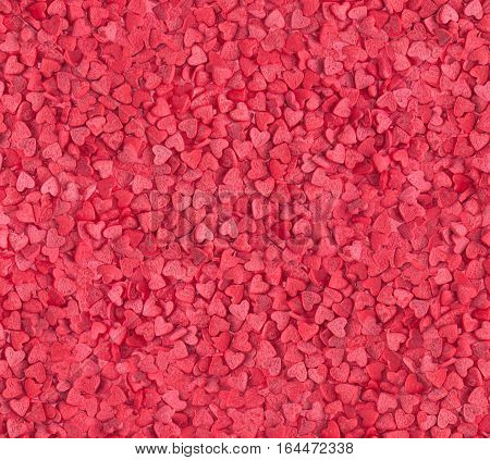 Seamless love background, red hearts candy sprinkles for food decoration.