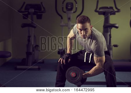 Young muscular built athlete working out in a gym sitting on a weightlifting machine and lifting two dumbbells