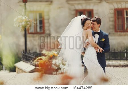 Groom Holds Bride's Waist Tenderly Standing In The Middle Of Old City Square