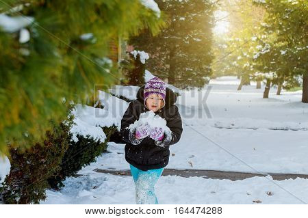 Happy little kid is playing in snow, good winter weather little girl playing in the street with snow