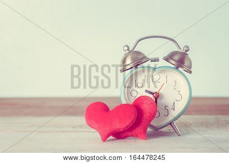heart alarm clock and heart shape on table Valentine's Day background