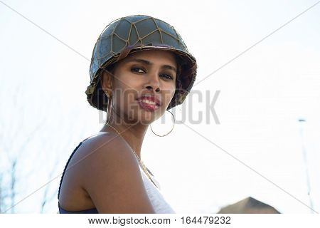 beautiful young woman with a ww2 military helmet