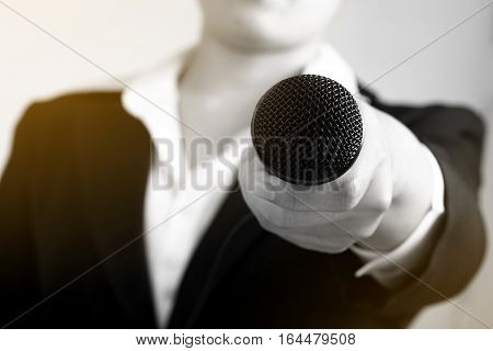 Interviewer making speech with microphone and hand gesturing concept for explaining interview selective focus.