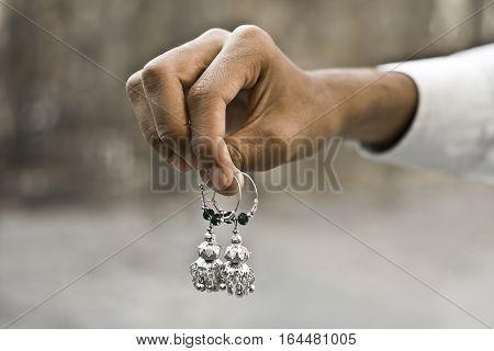 Human hand holding ornaments. viz. Bangles, earrings. etc.