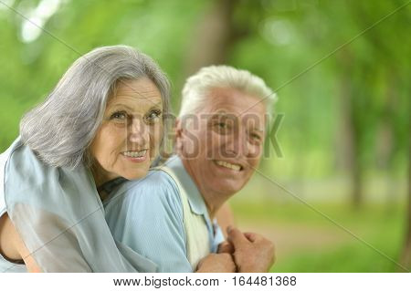 Senior couple in summer park on green background