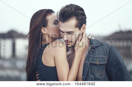 Young woman whispering love into boyfriend ear outdoors poster