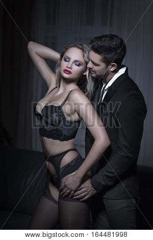 Rich man whispering young blonde lover in underwear sensuality and desire