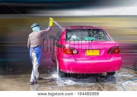 The worker wear gloves while the manual washing by high pressure water to pay a bubble of soap out of the car concept business car wash shop
