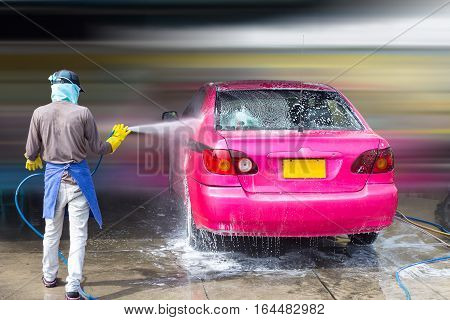 selective focus the worker is washing by high pressure water to pay a bubble of foam out of the car concept business car wash shop