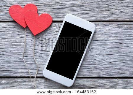 Valentine day internet sales concept, online shopping holiday background with copy space. Mobile phone on rustic wood with couple of red hearts, top view. Card and advertising mockup