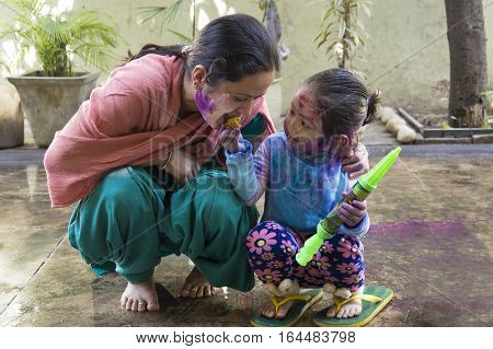 Mother and daughter with their face smeared with color celebrate Holi, the festival of colors in India.