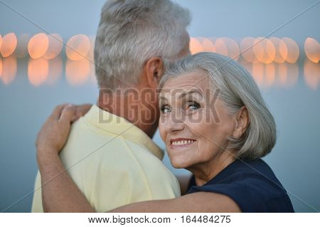 Happy senior couple  near river at summer, blurred background