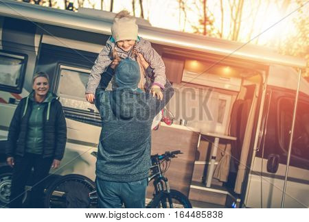 Family Camping Time. Young Family with Kid and Camper Motorhome During Autumn Camping Trip.