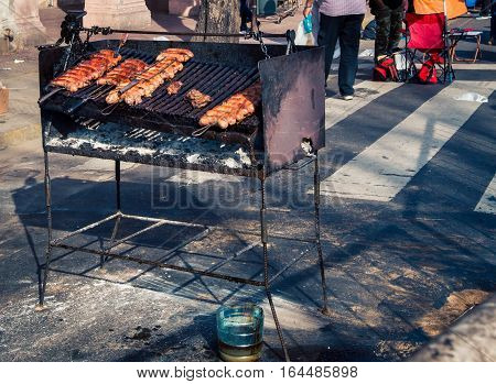Meat cooking on a grill at the Feria de Mataderos