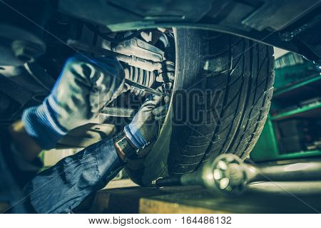 Car Mechanic Fixing Tie Rod and Steering System While Being Under the Vehicle. Car Maintenance in the Professional Service.