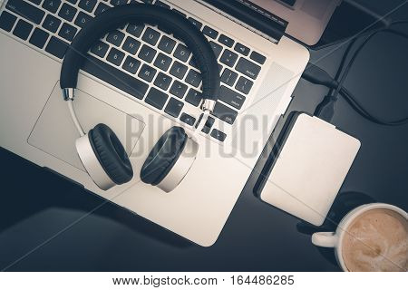 Freelance Worker Mobile Desktop Workstation. Laptop Computer Headphones Small Portable Hard Drive and Cup of Fresh Cappuccino Coffee on Black Glassy Desk Surface. Freedom of Freelance Work Concept.
