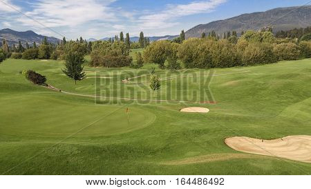 Mountain Golf Course:  Rolling green hills and mountains create an attractive setting for golf on a sunny day in British Columbia.