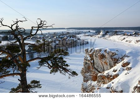 Winter view to the church of St. George and icy Chusovaya river. Russia, Sverdlovsk region, Sloboda Village.