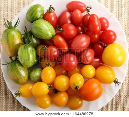 Colorful different kind tomatoes on white plate.