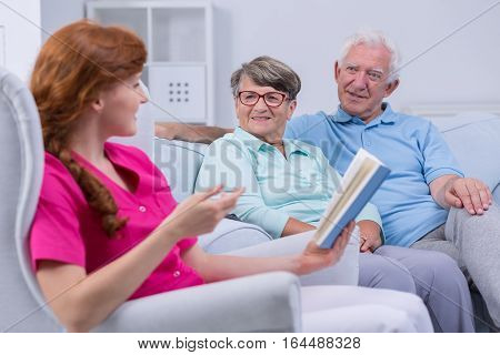 Caregiver Reading To Elderly Couple
