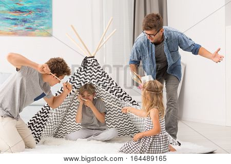Dad Reading Book And Children Playing