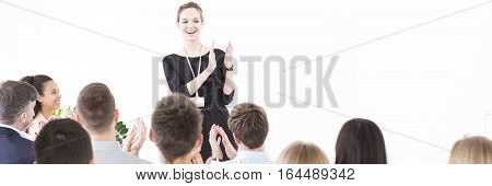 Cheerful corporate worker leading a meeting and clapping her hands together with other participants
