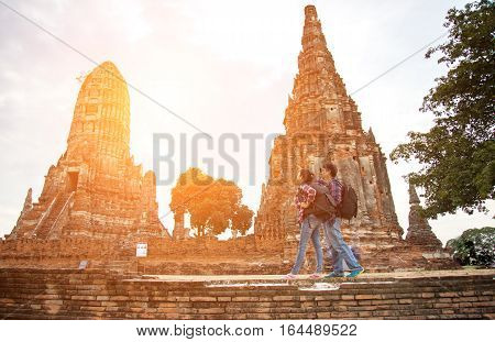 Traveler man and women with backpack walking in temple Ayuttaya Thailand