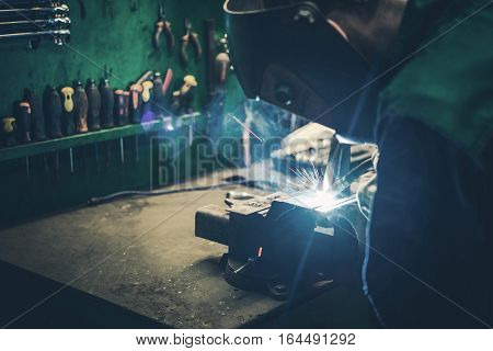 Welder Fusing Metal Together. Welding Metal Parts in the Small Workshop.