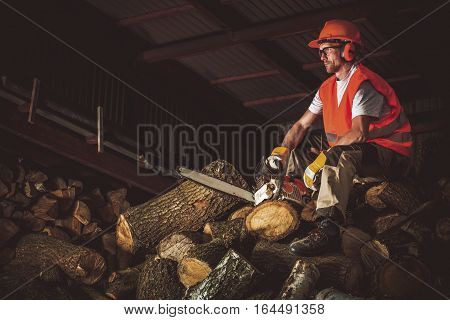 Wood Cutting Work. Caucasian Worker Resting on Pile of Chopped Firewood.