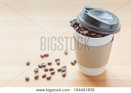 A paper cup of full roasted aroma coffee beans selective focus on paper cup and blurred background of fallen coffee beans on wooden board.