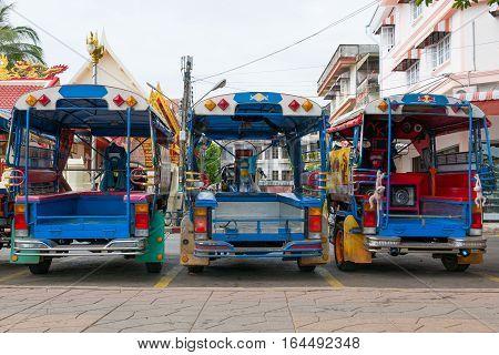 Blue funny rickshaws (tuk tuk) lined up in the street of Bankok Thailand. Rear view.