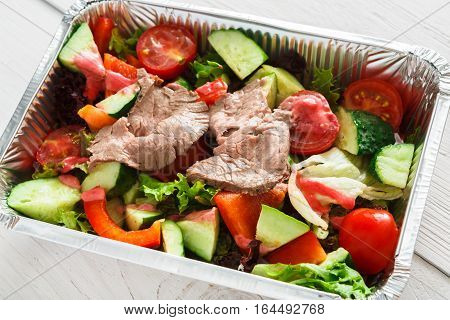Healthy eating concept. Lunch foil box, take away organic restaurant food. Weight loss diet. Steamed beef veal with fresh vegetable salad from tomatoes and cucumbers on white wood, closeup