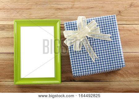 Blue gift box place near Green wooden frame on the wood floor in concept of Christmas and New year.