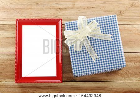 Blue gift box place near Red wooden frame on the wood floor in concept of Christmas and New year.