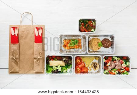 Healthy food delivery. Take away of natural organic fitness dishes for diet. Daily ratio nutrition pyramid meals in foil boxes on white wood. Craft package, meat and salads. Top view, flat lay