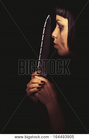 Killer profile. Murderous woman. Domestic crime. The profile of a young woman with a knife in her hand. In the darkness her face is illuminated. Crying. Home violence.