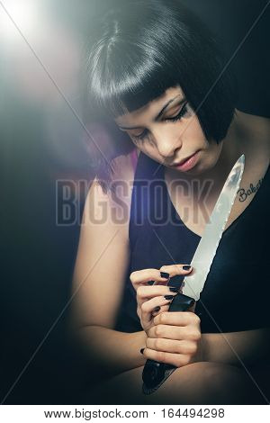 Murderous suicide girl with knife. Crime concept. A beautiful girl with a knife in her hand has just committed a crime. She is touching the blade watching the knife. On the knife is reflected her look with open eyes. Black background.