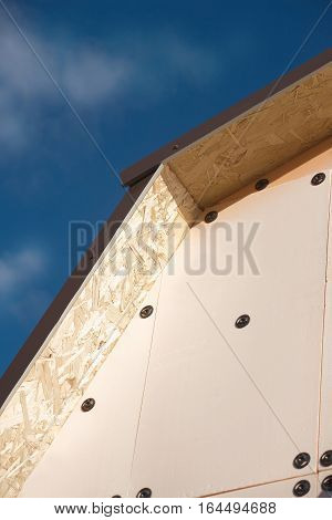 Roof of a country house covered with brown metal tile and wall with insulation closeup against blue sky with white clouds vertical view